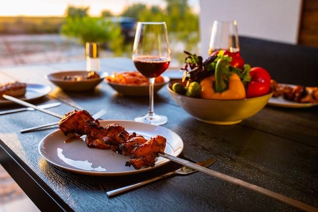 Gegrilltes fleisch wird zu hause serviertgegrilltes fleisch mit wein und gemüsesommer auf der terrasse