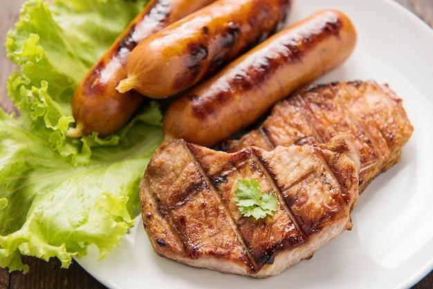 Gegrilltes fleisch, würste und gemüse auf tellerabschluß oben.
