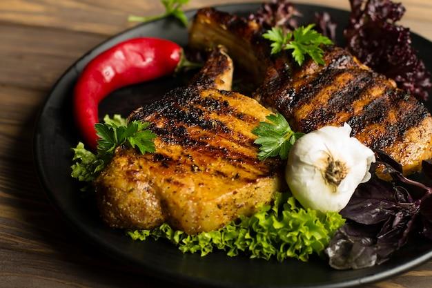 Gegrilltes fleischsteak mit gewürzen, knoblauch und pfeffer auf einem schwarzen teller.