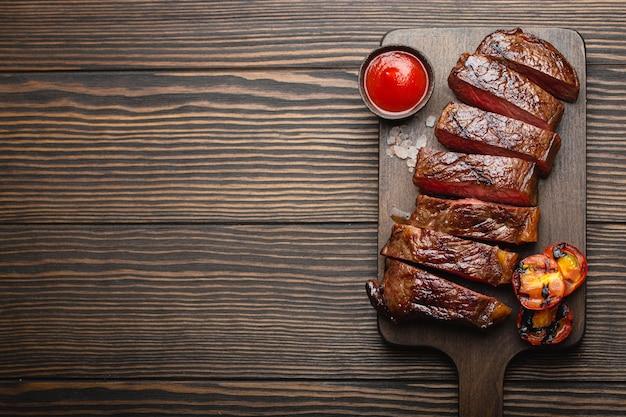 Gegrilltes/gebratenes und in scheiben geschnittenes marmoriertes fleischsteak mit gabel, tomaten, tomatensauce/ketchup auf holzbrett, draufsicht, nahaufnahme mit platz für text, rustikaler hintergrund. rindfleisch steak-konzept
