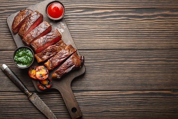 Gegrilltes/gebratenes und in scheiben geschnittenes marmoriertes fleischsteak mit gabel, tomaten, verschiedenen saucen auf holzbrett, draufsicht, nahaufnahme mit platz für text, rustikaler hintergrund. rindfleisch steak-konzept