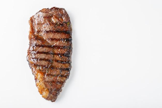 Gegrilltes gemarmortes rindfleischsteakstreifenfilet lokalisiert auf weißem hintergrund, draufsicht mit kopienraum