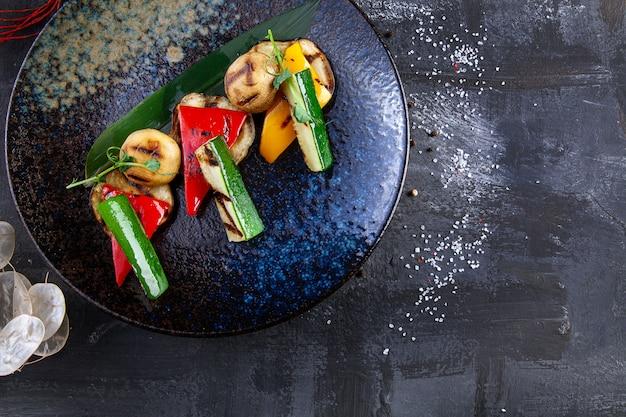 Gegrilltes gemüse, tomaten, pfeffer, pilze und gurken. moderne küche. gesundes essen mit platz zum kopieren. frisches veganes mittagessen.