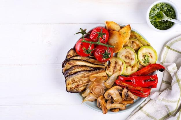 Gegrilltes gemüse und grünes pesto auf heller oberfläche