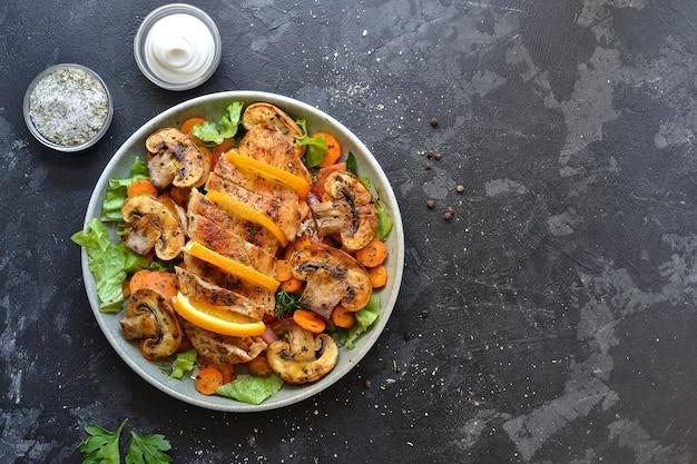 Gegrilltes gemüse und hähnchenbrustsalat. hühnerbrust, salat, pilze, tomaten, orange.