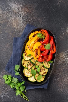 Gegrilltes gemüse zucchini, roter und gelber pfeffer, paprika und korianderbouquet auf grillpfanne. ansicht von oben. grillkonzept.