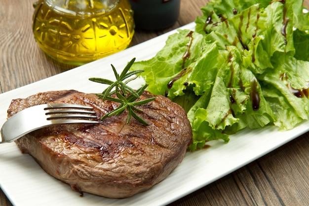 Gegrilltes geschnittenes fleischfilet auf teller und salat