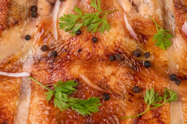 Gegrilltes hähnchen auf dem teller mit chili-knoblauch und mit pfeffersamen bestreut.