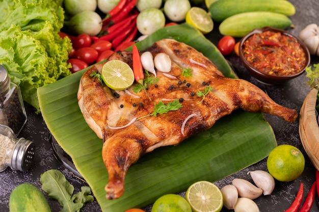 Gegrilltes hähnchen auf einem teller mit chilischoten, knoblauchsauce und mit pfeffersamen bestreut.