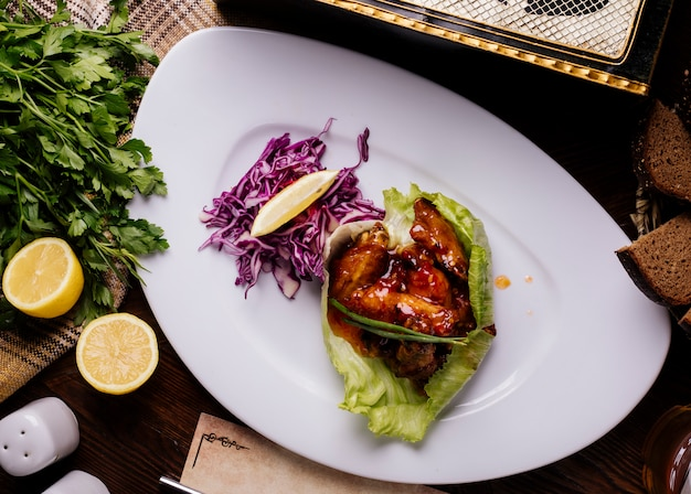 Gegrilltes hähnchen in teriyaki-sauce mit rotem cabbahe, kräutern und zitrone.