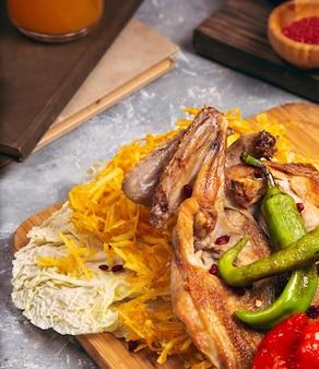 Gegrilltes hähnchen in verschiedenen variationen mit kirschtomaten, grüner paprika auf einem holzbrett.