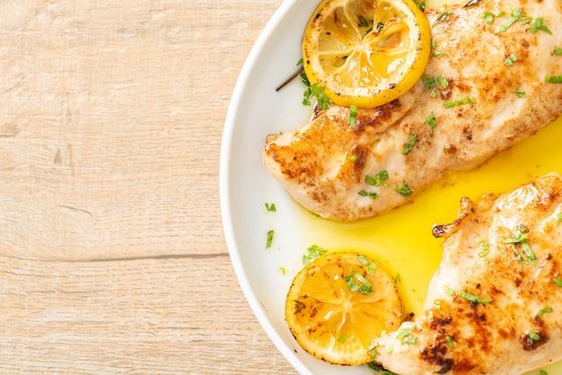 Gegrilltes hähnchen mit butter, zitrone und knoblauch auf weißem teller