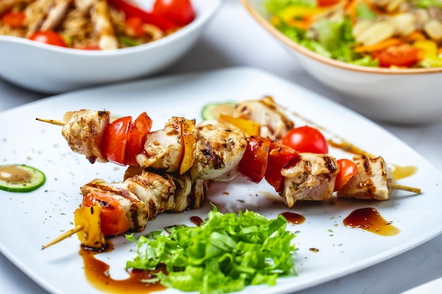 Gegrilltes hähnchen mit seitenansicht gegrilltes hähnchen mit tomaten-paprika-sauce und salat auf einem teller