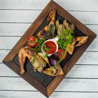 Gegrilltes hähnchen mit tomaten, kräutern und barbecue-sauce.