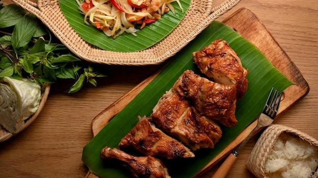 Gegrilltes hähnchen nach thailändischer art mit somtum- oder papayasalat und klebreis traditionelles thai-essen