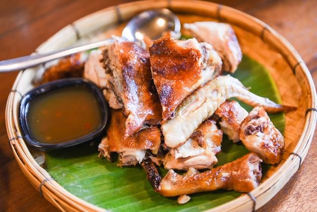 Gegrilltes hähnchen-thai-essen mit chilisauce auf bananenblatt und holz
