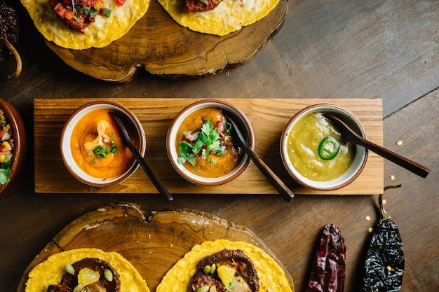 Gegrilltes hähnchen und foie gras tacos serviert auf holz schneidebrett mit verschiedenen soßen.