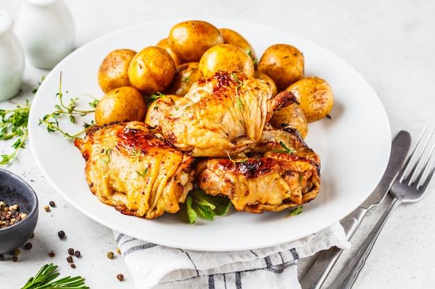 Gegrilltes hähnchen und ofenkartoffeln in einer gusseisernen pfanne.