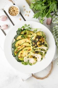 Gegrilltes hähnchenfilet mit grüner kräutermarinade, gebratenen zucchini und pinienkernen