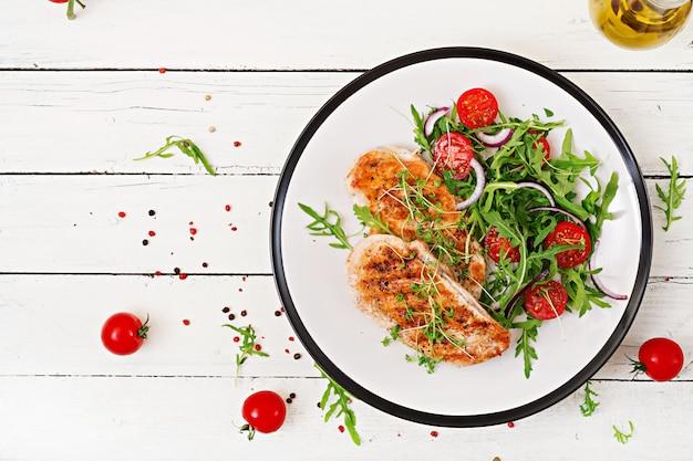 Gegrilltes hähnchenfilet und frischer gemüsesalat aus tomaten, roten zwiebeln und rucola. hühnerfleischsalat. gesundes essen. flach liegen. ansicht von oben.