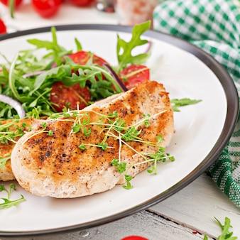Gegrilltes hähnchenfilet und frischer gemüsesalat aus tomaten, roten zwiebeln und rucola. hühnerfleischsalat. gesundes essen.