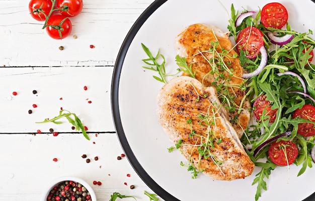 Gegrilltes hähnchenfilet und frischer gemüsesalat aus tomaten, roten zwiebeln und rucola.