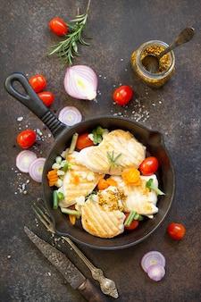 Gegrilltes hähnchenfilet und verschiedenes gemüse auf einer gusseisenpfanne