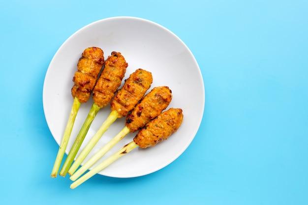 Gegrilltes hähnchenhackfleisch mit curry-paste und kokoscreme auf zitronengras-spießen.