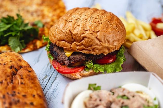 Gegrilltes hamburger-rindfleischpastetchen von der seite mit käsetomaten-salat und pommes frites auf dem tisch