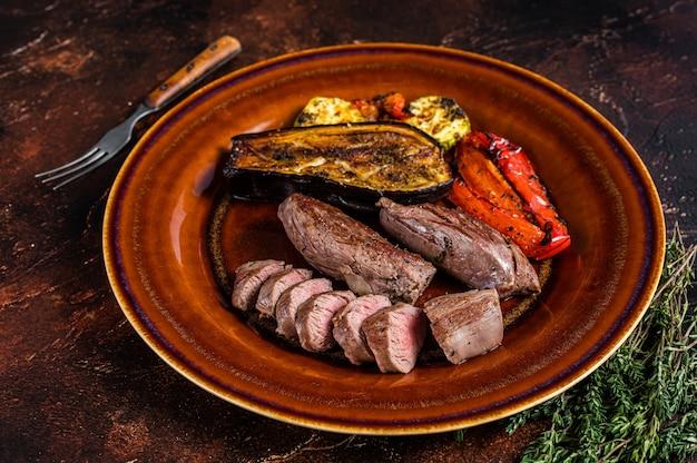 Gegrilltes hammelfilet filetfleisch, lammfilet auf rustikalem teller mit gemüse. draufsicht.