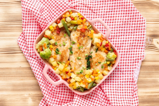 Gegrilltes hausgemachtes huhn mit verschiedenen köstlichen gemüsen auf einem hellen hölzernen hintergrund. draufsicht.