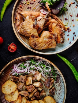 Gegrilltes hühnchen, rindfleischeintopf und kartoffelchips mit zwiebeln und grünem salat in platten.