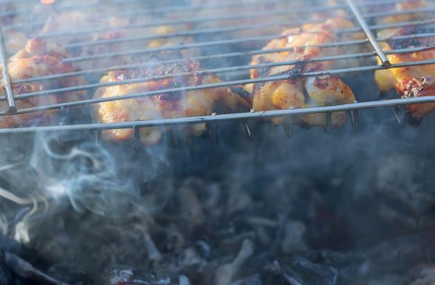 Gegrilltes hühnerbein über flammen auf einem grill.