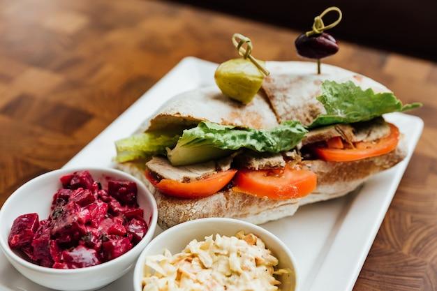 Gegrilltes hühnersandwich mit brot, tomaten und salat serviert mit rote-bete-salat.