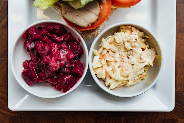 Gegrilltes hühnersandwich mit brot, tomaten und salat serviert mit rote-bete-salat