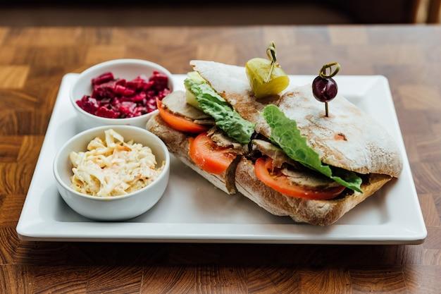 Gegrilltes hühnersandwich mit hausgemachtem brot, tomaten und salat mit rote beete