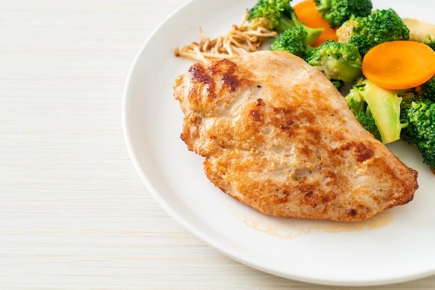 Gegrilltes hühnersteak mit gemüse auf weißem teller