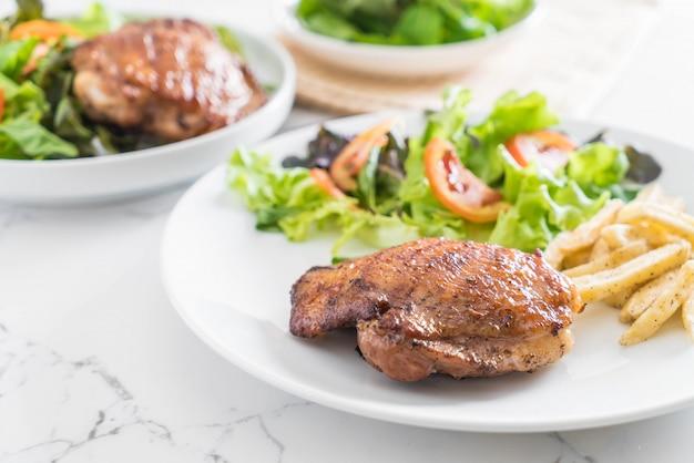 Gegrilltes hühnersteak mit pommes frites und gemüsesalat
