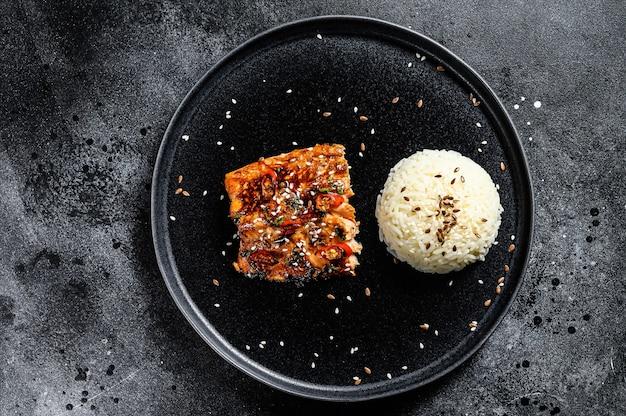 Gegrilltes japanisches teriyaki-lachsfilet, glasiert in köstlicher sauce mit einer beilage reis