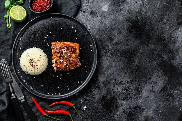 Gegrilltes japanisches teriyaki-meerforellenfilet, glasiert in köstlicher sauce mit einer beilage reis.