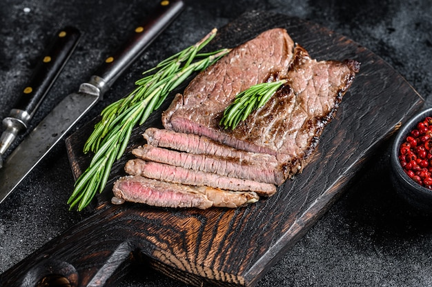 Gegrilltes kalbsfleisch-kotelettsteak auf einem schneidebrett. schwarzer hintergrund. draufsicht.