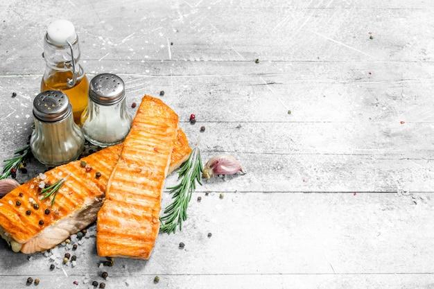 Gegrilltes lachsfilet mit gewürzen und rosmarinzweigen. auf einem rustikalen tisch.