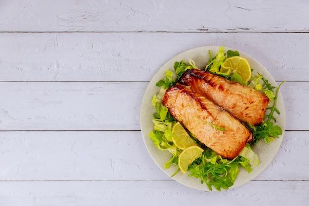 Gegrilltes lachsfilet mit grünem salat auf grauem teller. draufsicht.