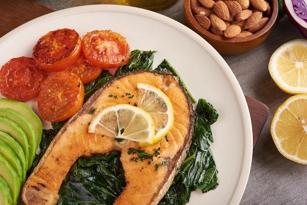 Gegrilltes lachsfischfilet und frischer grüner salatgemüsetomatensalat mit avocado-guacamole. ausgewogenes ernährungskonzept für eine saubere, flexible mediterrane ernährung.