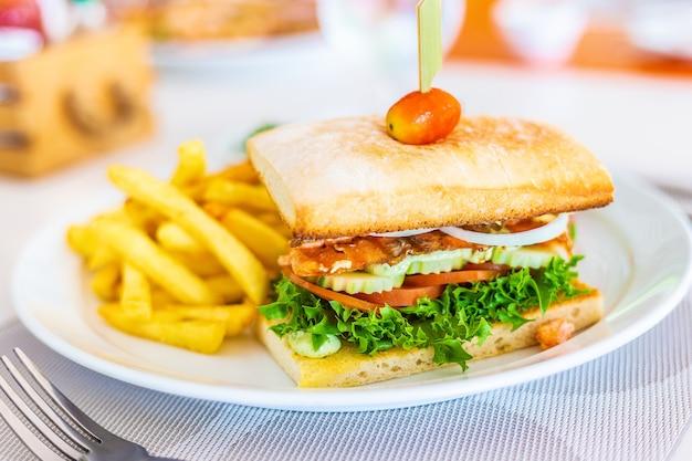 Gegrilltes lachssandwich mit pommes-frites auf weißer platte
