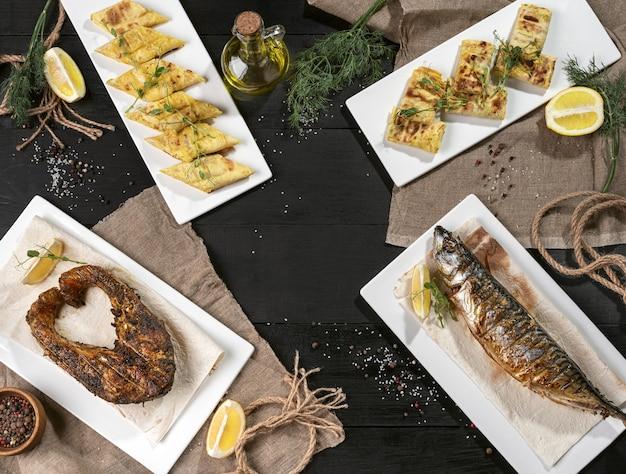 Gegrilltes lachssteak gebackene makrele und brötchen von dünnem fladenbrot auf schwarzem tisch