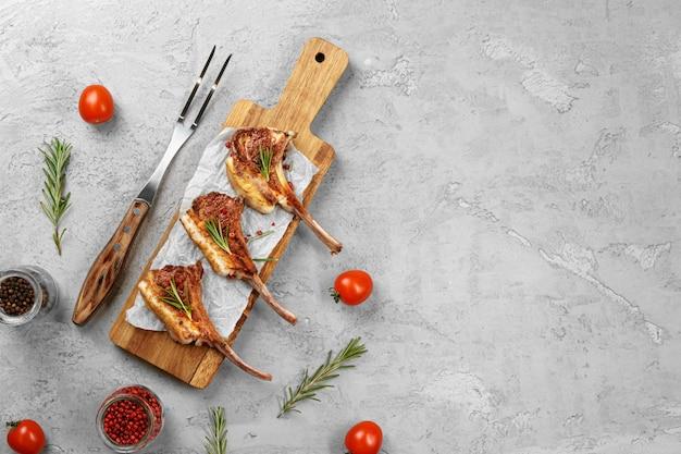 Gegrilltes lammkarree serviert auf einem holzbrett