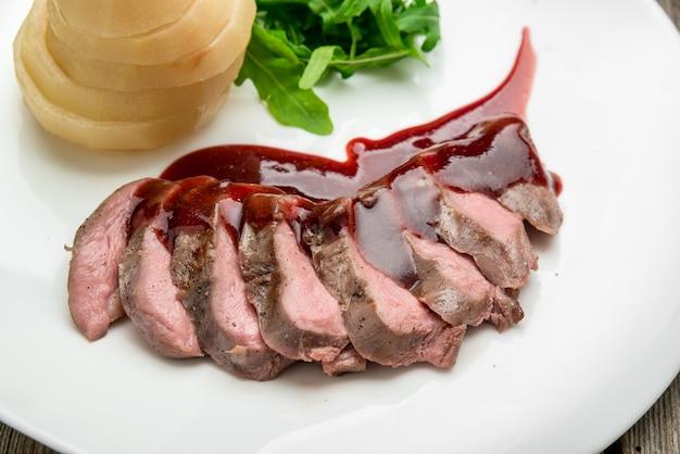 Gegrilltes mittleres seltenes rindfleisch mit birne, gegrilltes gemüse, auf hölzernem hintergrund schließen oben.