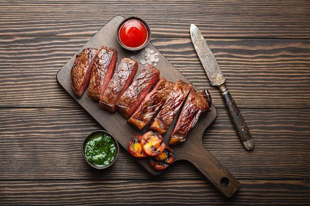 Gegrilltes oder gebratenes und in scheiben geschnittenes marmoriertes fleischsteak mit gabel, tomaten als beilage und verschiedenen saucen auf holzschneidebrett, draufsicht, nahaufnahme, rustikaler holzhintergrund. rindfleisch steak-konzept