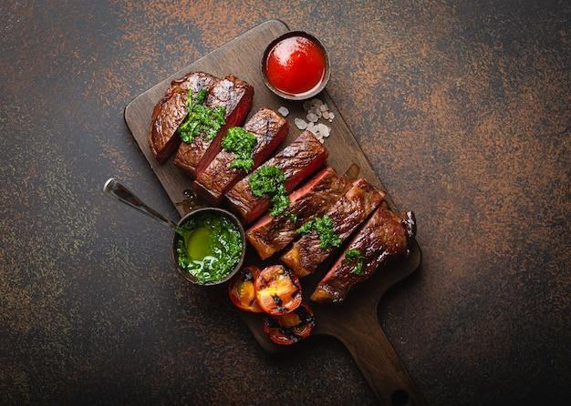 Gegrilltes oder gebratenes und in scheiben geschnittenes marmoriertes fleischsteak mit gabel, tomaten als beilage und verschiedenen saucen auf holzschneidebrett, draufsicht, nahaufnahme, rustikaler steinhintergrund. rindfleisch steak-konzept